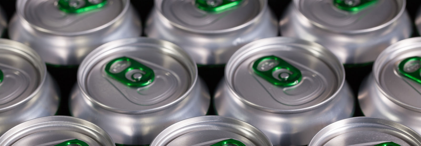 green tabs on top of aluminum Heineken cans in a group