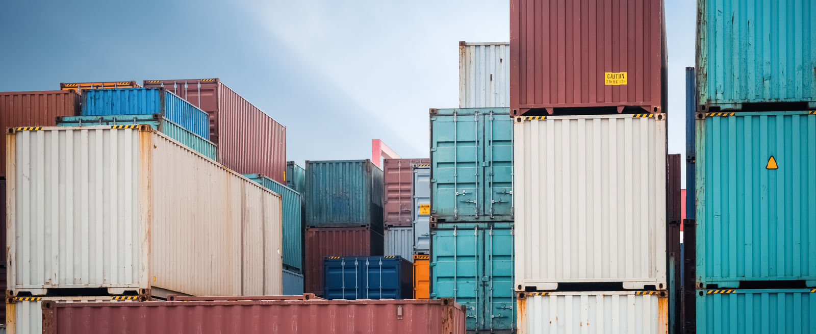 red white and blue shipping containers stacked in storage yard