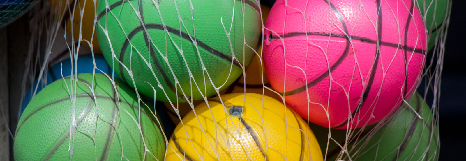 multiple colorful basketballs stored away in torn ball bag