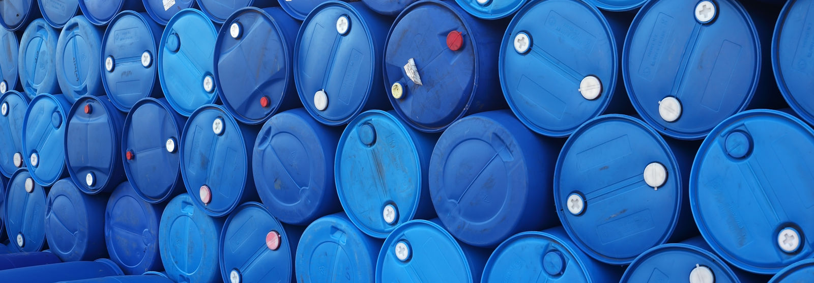 blue drums sealed and stacked in line