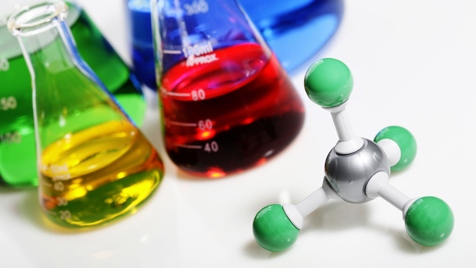 Beakers filled with chemicals on white surface