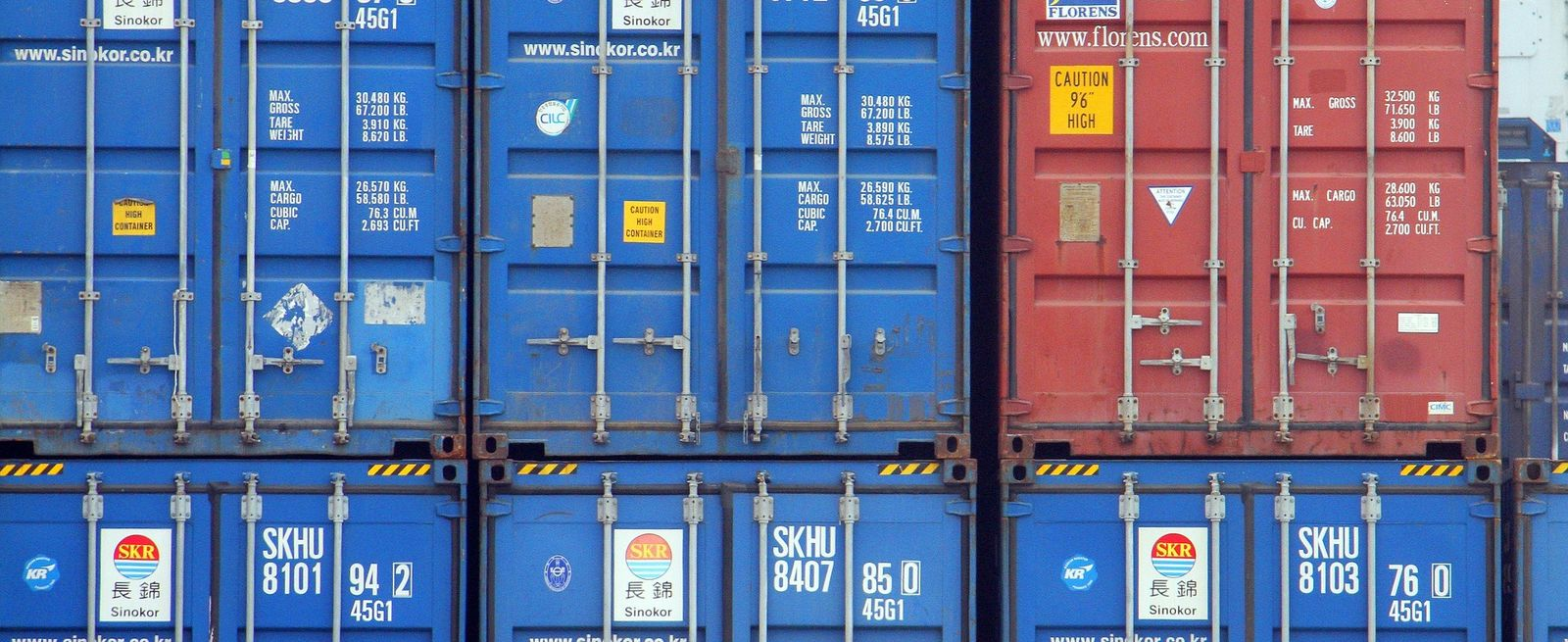 back end of blue and red cargo containers stacked