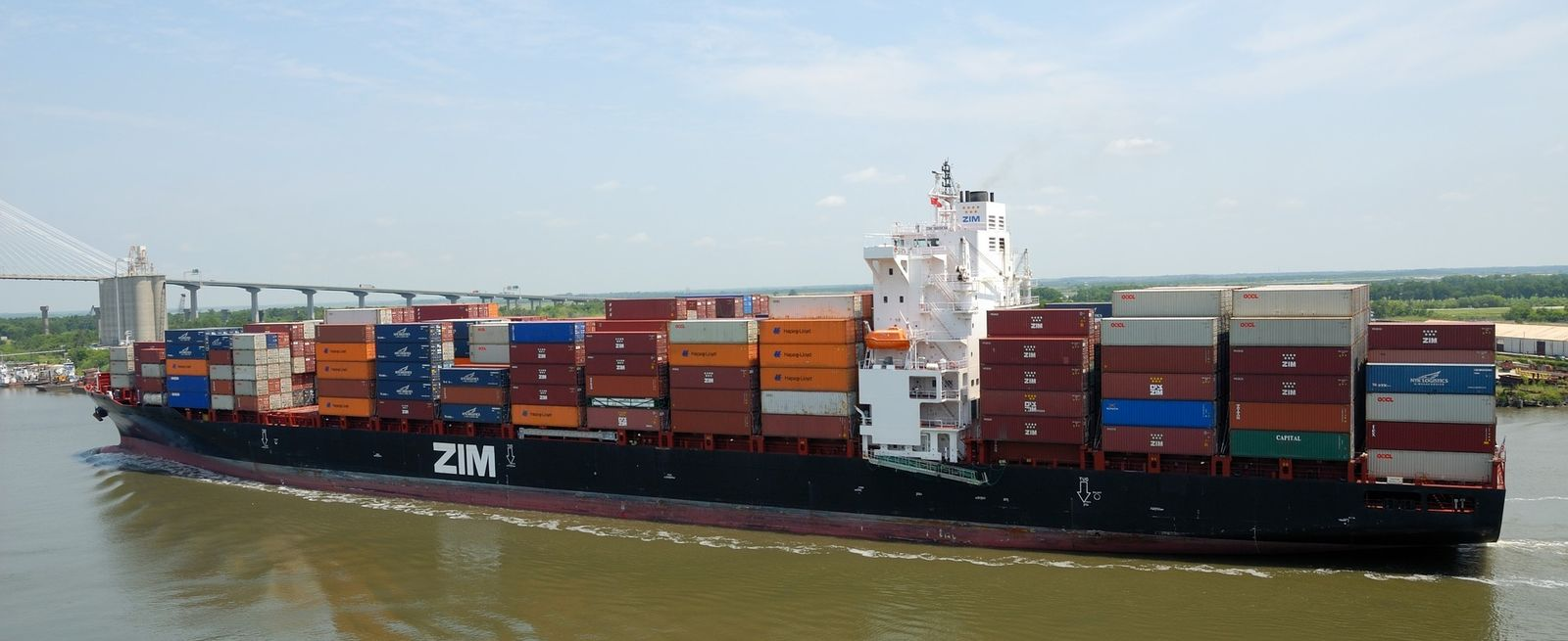 ZIM ship moving on water with stacked cargo containers