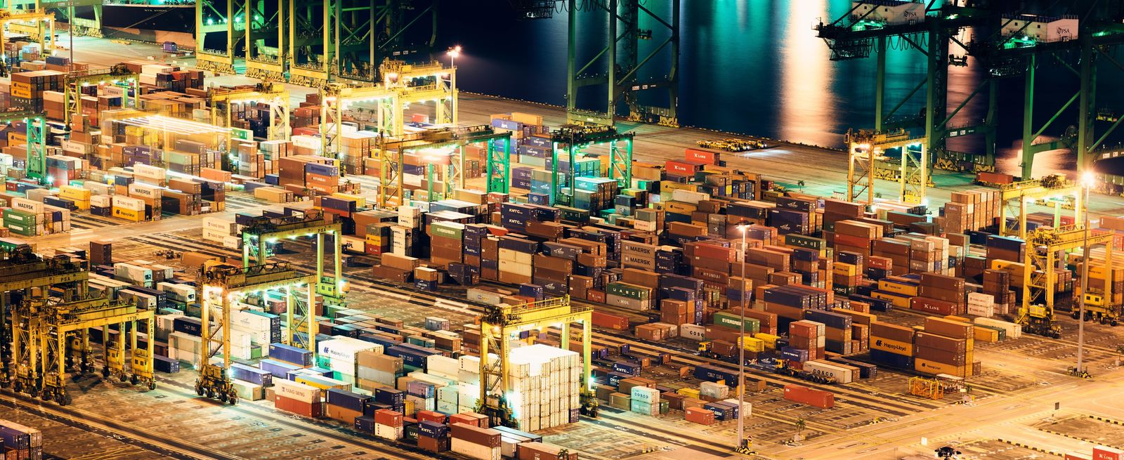 cargo containers at port yard lighted at night by bright lights